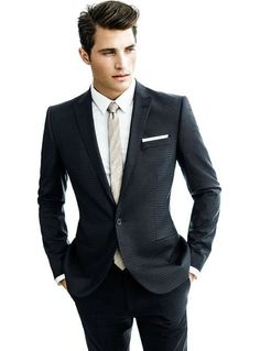 Patterned black suit, white dress shirt and silver diagonal-striped tie with white pocket square.