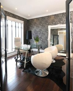 White  black modern office design with white  black wallpaper, Polished chrome glass-top sawhorse desk, white leather padded office chair, black cowhide rug, white pod chairs, white ornate baroque floor mirror and glossy black floor lamp.