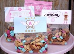 Cowgirl trail mix as party snack or packaged as favor. Instead of nuts, you could use Utz wagon wheel pretzels, raisins, banana chips, pink and brown m&ms, chex cereal, and Kraft caramel bits