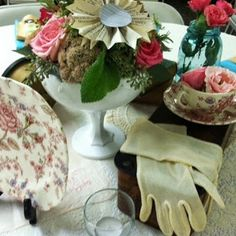 Vintage gloves, clocks, chintz china teacups and old sewing machine drawers on a lace overlay with vintage hanky, made this centerpiece beautiful, nostalgic and interesting Design by Marietta Hartley floral by Kelly Quinn
