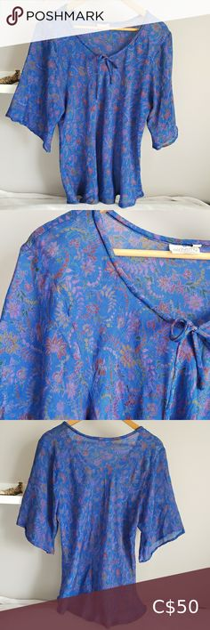 Alchemy Recycled Silk Flutter Sleeve Blouse L Alchemy Eco-Fashions recycled silk blouse from an ethical/sustainable BC company. Made in India from 100% recycled silk saris! Bias-cut design with lovely drape. Scoop neck with tie. Three quarter length flutter sleeves. Rounded hem. Gorgeous blue silk with floral print. A few flaws, see photos: largest is on front shoulder, a few other small runs on back. Flaws are not very noticeable due to print of fabric. Size is XL but would fit a medium or… Buffalo Shirt, Sheer White Blouse, Black Bustier, Satin Blouses, Wrap Blouse, Tweed Jacket, Printed Blouse, Flutter Sleeve, Gray Dress