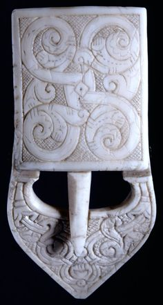 Walrus ivory buckle, Scotland, Upper part with tongue, turning on piece of copper wire; front surface engraved with floral designs on hatched background