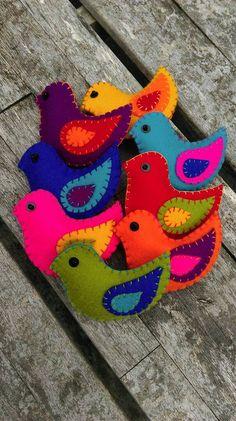 Colorido fieltro pájaros percha de la pared / por HetBovenhuis