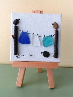This original pebble art picture was created with beach glass, twigs and stone pebbles on 3x3 canvas board mounted on a small wooden easel. It features a three birds and a clothesline. Buyer has the option of choosing a black or natural colored easel. Please specify your easel color choice when ordering. If not specified a random color will be selected. Thank you for looking and have a nice day.