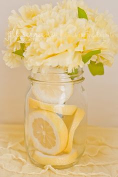 Gorgeous floral centerpiece with lemons and water or floating candles instead of flowers.