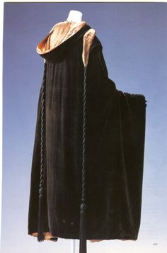 Madeleine Vionnet Evening Cape. c. 1923. Dark brown velvet; hooded; warp used in vertical orientation; red and brown lamé for lining; two cords with rayon tassels.