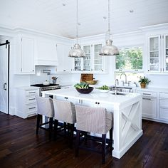 ****white Muskoka country cottage kitchen with dark wood floors, quartz counters, high rise faucet, industrial style pendant lights, closed and glass door Shaker cabinets, paint Chantilly Lace (OC-65), Benjamin Moore, designer Cameron MacNeil, Ontario, Canada