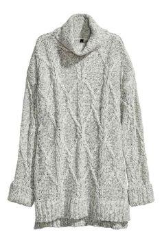 Jersey en punto trenzado: Jersey largo en punto trenzado suave con lana en la trama. Cuello alto, hombros caídos, mangas largas con puños vueltos cosidos y pequeñas aberturas en los laterales.