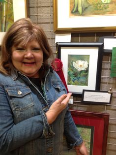 "Karen Scherrer, Texas Watercolor Artist standing next to her ""Wild Poppy Painting"""