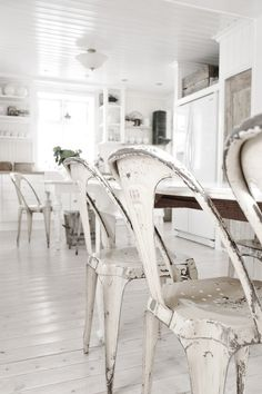 Love this white on white kitchen from the painted hardwood floor to the time worn chipped paint of the industrial dining chairs.