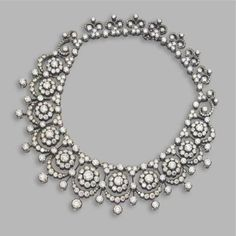 A diamond tiara necklace, early 20thC, featuring eleven diamond clusters, each topped with an arch and circular diamonds. Sold via Sotheby's in 2009.