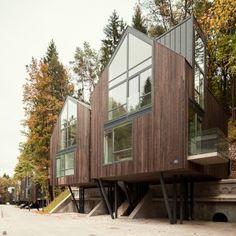 Timber-clad houses raised up on stilts over ammunition vaults in Vilnius parkland