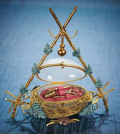 This gilt bird's nest necessaire graces the cover of the catalog. Nestled within the translucent, hinged glass egg are scissors, thimble, awl, and needle.