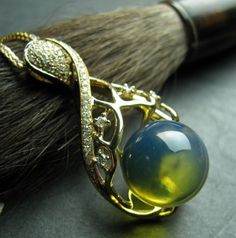 14k gold necklace with blue amber orb and diamond pave accents