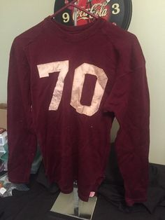 very old football jersey. I can't find anything on the company or year it might be from. It has the original tag on the tail of the jersey. It's made by Trojan in Ionia, Mich. It has a size 42 tag on the tail.  $199