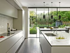 Sleek, minimalist, modern kitchen design in Wandsworth with handle-less cabinets. Large island with integrated sink and pendant lighting. Sliding glass wall looking out to landscaped patio and garden.
