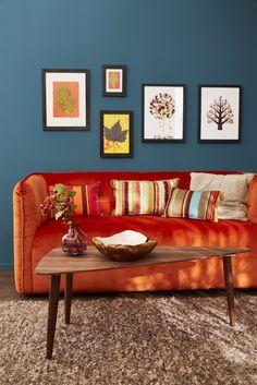 Auffälliges Couchsofa vor petrolfarbener Wohnzimmerwand. Schön finden wir auch den Walnuss-Couchtisch!