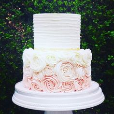 Traditional white layer wedding cake with blush pink ruffled base