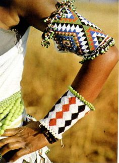 Model wearing Zulu (South Africa) beadwork arm adornments ~ known as izingusha.