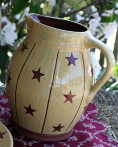 """Redware Star Pottery, by K & K Interiors. Antique mustard stoneware with red stars and a fine crackle in the glaze for an aged appearance. This is for the PITCHER, which is red on the inside. Measures 8"""" x 6"""". This is a really neat primitive looking set, fabulous displayed in antique hutches or cabinets!"""
