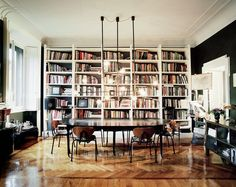 Dark dining space with wall of bookshelves, modern light fixtures, and black walls // Italian design
