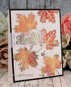 handmade Thanksgivng card from leescraps.blogspot.com ... directions on the blog ... maple leaves stamped with Distress Inks in oranges ... matching stamp with leaf veins embossed in gold ... sentiment in gold on a vellum banner ... splatters of gold watercolor top add a playful touch ... luv the variegated colors on the leaves ....