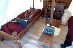 """This is my most recent interpretation of a medieval pavilion interior.  The bed is based on a 10th century design, although you see examples of it in later medieval art.  I bought it from craftedqualityplus.com/Beds/beds.html  The tent is the Regent Pavilion from Panther Primitives and I've used it for six years now.  The trunks I picked up at various chain stores through the years.  I'm always on the lookout for something that looks """"medieval""""."""