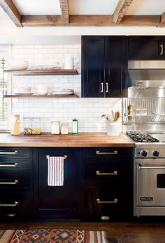Dark kitchen cabinets with open shelves and brass hardware.
