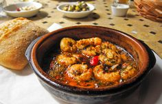 Shrimp Pil Pil ---- This is a wonderful dish that I had while living in Barcelona. It is best served with a good white wine or sangria, and warm crusty bread.  This was given to us by the owner of a small cafe in Barceloneta.  You'll want to have plenty of bread on hand to capture the delicious pan juices from these garlicky crustaceans. This Basque tapa is traditionally served at the table sizzling (pil pilean-doin) in a little metal pan.