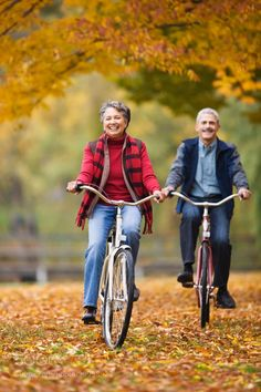 African couple riding bicycles in park in autumn by gabledenims