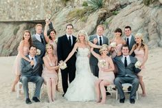 bride and groom posing with bridal party on the beach, groomsmen in grey suits, bridesmaids in short peach dresses and bride in mermaid lazaro lace dress http://www.itgirlweddings.com/blog/cabo-san-lucas-wedding