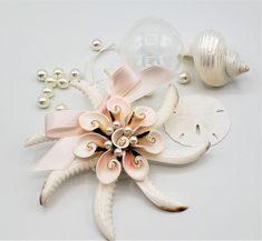 """Beach Christmas seashell ornament in gorgeous blush pink! Back by popular demand, this simple but gorgeous shell pinwheel ornament is simply beautiful!  Large cowrie shell cuts and strombus shell cuts give its amazing natural blush pink colors. It's all built on a capiz shell round base for strength and we add a perfectly matching blossom pink bow that, frankly, just makes it!!  5"""" average diameter."""
