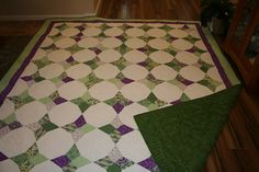 Periwinkle Quilt in greens and purple.  It was longarm quilted with 4 different patterns.