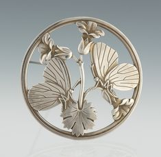 A Georg Jensen Sterling Silver Brooch    Width 2 in.  Sterling silver brooch of circular shape with flower and butterfly design, number 283. Back stamped with Jensen hallmarks, second half of 20th century.