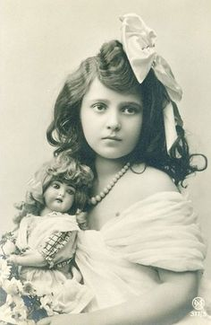 Beautiful old photo of a little girl posing with her doll