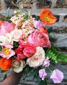 A pink wedding bouquet full of orange and blush flowers. | Fleur