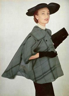 Model in figure-hugging black dress worn with light sheer organza plaid jacket by Grés, hat by Gilbert Orcel, photo by Pottier, 1951