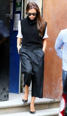 Victoria Beckham in a black sleeveless turtleneck, white shirt, black pants, black heels, and sunglasses