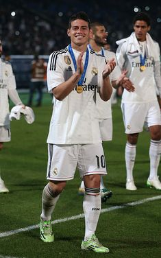 James Rodriguez and Real Madrid's players celebrate with the trophy after winning the FIFA Club World Cup final football match against San Lorenzo at the Marrakesh stadium in the Moroccan city of Marrakesh on December 20, 2014. Real Madrid defeated San Lorenzo of Argentina 2-0 to win the Club World Cup and secure their fourth trophy of 2014