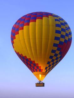 Hot air balloons flying low over the Rio Grande River just after sunrise, Albuquerque International Balloon Fiesta, Albuquerque, New Mexico.