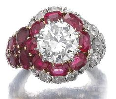 Ruby and diamond ring, Van Cleef & Arpels.     The circular-cut diamond weighing 3.17 carats, within a surround of cushion-shaped and circular-cut rubies and circular-cut diamonds, size 46, sizing beads, indistinctly signed V.C.A. and numbered, French assay marks.     Sotheby's.