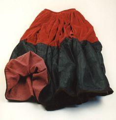 Der Rock gehört zur Probsteier Festtagstracht des 19. Jahrhunderts. Er ist unterteilt. Oben besteht er aus rotem Samt und unten aus schwarzer Seide mit braunem Samtstoßband. Das Futter ist aus grobem lila Köper. #Probstei