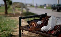 [Foto del día]    Una mujer pakistaní y su hijo duermen bajo la sombra de un árbol, muchos pakistaníes duermen en las calles para evitar el calor de sus hogares durante el verano. (AP Photo/Muhammed Muheisen) AP