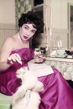 Elizabeth Taylor, feeding tidbits from her table to a pet poodle.   ca. 1955   Photo by Silver Screen Collection/Getty Images