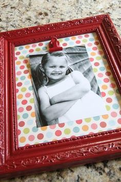 Spray paint a cheap frame, take out the glass and replace it with scrapbook paper, hot glue a clip and change the picture whenever you want!  Great idea for my office!!
