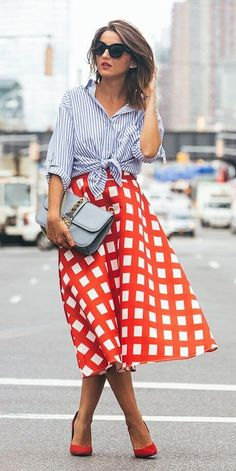 Stylish brunette in check midi skirt and striped shirt