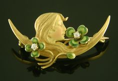 An exquisite, petite brooch of a woman serenely dreaming amid lucky clovers. The woman's profile and the four-leaf clovers are beautifully enameled in soft pastel shades. The clovers are set with sparkling dew drop-like diamonds. Created by Krementz & Company in 14kt gold, circa 1900.