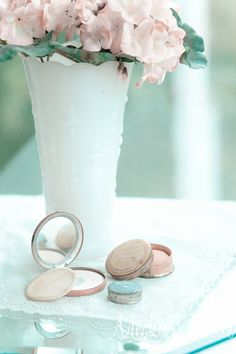 pastel flowers in vase with little make up compacts