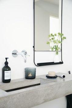 wastafelblad van cement in een witte badkamer