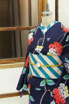 濃紺色の地に、レモンイエローとポピーレッド、グレープパープルとスカイブルーが優しくぼかされた飴細工のような澄んだ綺麗な色合いがノスタルジックな詩情をさそう紫陽花模様が染め出された注染レトロ浴衣です。